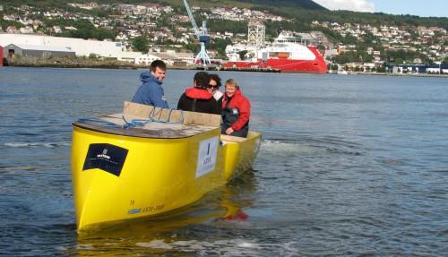 Skipsdesignere tester ut en X-Bow-modell, med et ekte X-Bow-skip i bakgrunnen. Foto: Ulstein Verft