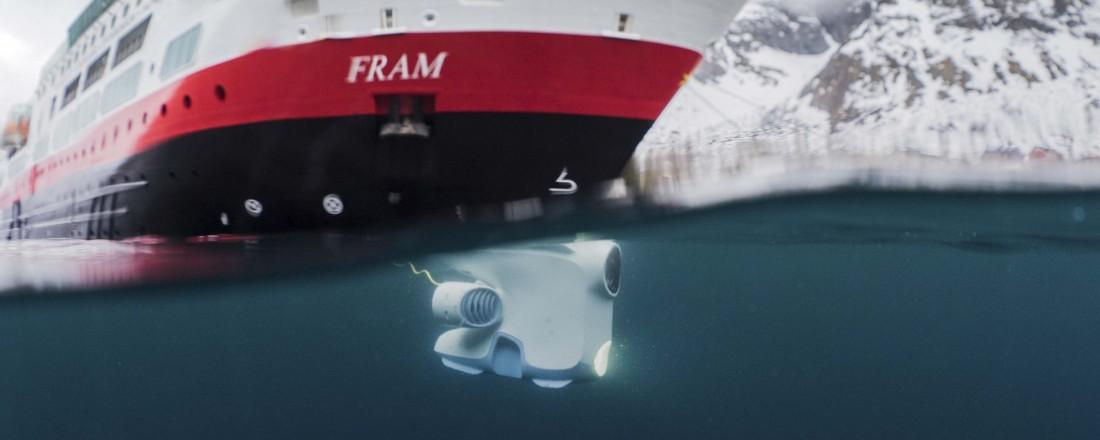 Her utforsker en Blueye-undervannsdrone farvannet ved ekspedisjonsskipet MS Fram utenfor norskekysten i vår. Nå skal Hurtigruten ta den norskutviklede dronen ut på verdenshavene. Fotomontasje: Blueye/Hurtigruten