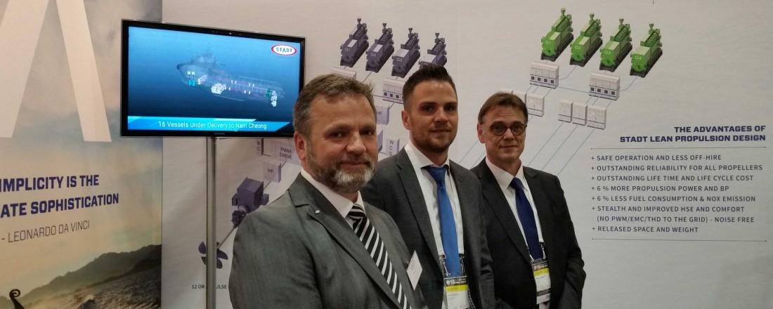 Frå venstre: Hallvard Slettevoll, Daniel Slettevoll og Webbjørn Hageselle på Stadt sin stand under årets Nor-Shipping. Foto: Stadt