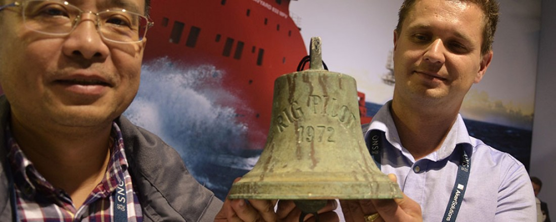 Skipsklokka frå det første norskbygde forsyningsskipet, Rig Pilot, er komen heim og blei for første gong vist fram under oljemessa i Stavanger onsdag. Frå venstre Mao Liling og Tor Arne leine, begge tilsett i Havyard. (Foto: Thomas Førde)